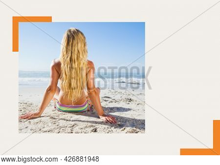 Photograph of rear woman sunbathing at the beach against grey background. summer holiday and vacation concept