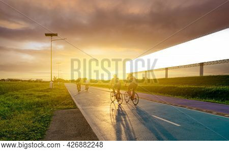 Sports Man Ride Bicycles On The Road In The Evening Near Blank Advertising Billboard With Sunset Sky
