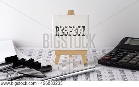 Text Respect On Easel With Office Tools And Paper.top View. Business