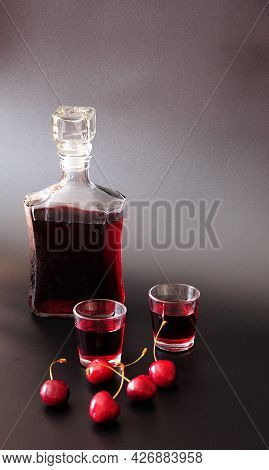 Cherry Liqueur, Two Glasses, A Bottle And A Handful Of Ripe Crane Berries On A Black Background.