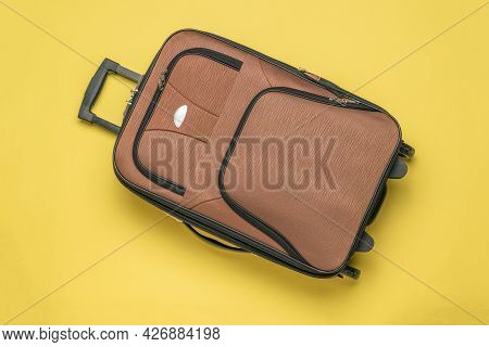 Brown Travel Suitcase On A Yellow Background. Equipment For Transporting Things On Trips. Flat Lay.