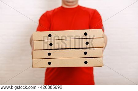 Man Holding Several Pizza Boxes. Delivery Food Service. Photo Of Happy Man From Delivery Service Giv