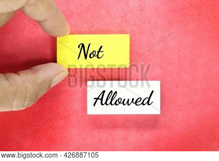 Hands Holding Colored Blocks With The Word Not Allowed