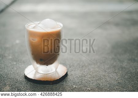 Iced Mocha Coffee In A Transparent Double Layer Cup On Wooden Saucer