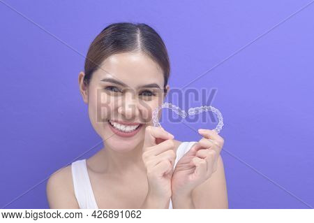 Young Smiling Woman Holding Invisalign Braces In Studio, Dental Healthcare And Orthodontic Concept..