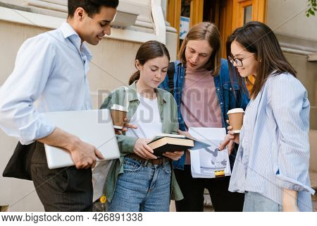 Multiracial students drinking coffee and talking to each other while standing outdoors