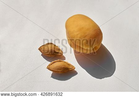 Apricot And Two Apricot Seeds On A Gray Textured Background. Fruit