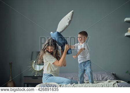 Funny Boy Throws Pillows At Mom, Pillow War, Happy Childhood. Motherhood, Child Aggression Concept