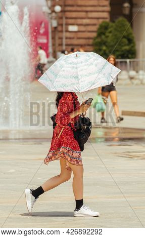 Girl Or Woman In Short Colorful Dress Walking In The City With Umbrella Protecting From The Sun, Ult