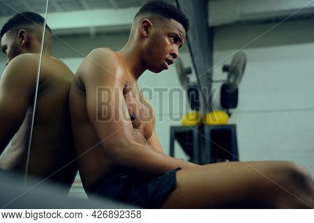 Young African American Male Athlete Resting In The Gym After A Hard Cross Training. Shirtless Mixed