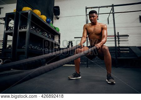 Young African American Male Exercising Inside A Gym. Topless Male Personal Trainer Using Rope To Str