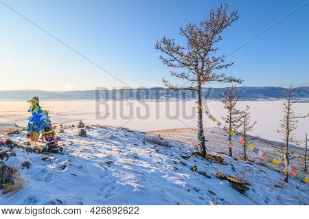View Of Lake Baikal From Top Of Sacred Hill With Buddhist Prayer Flags Hanging On The Tree. Tibetan