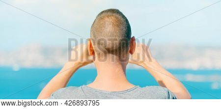a young caucasian man, seen from behind, takes a photo of the Mediterranean sea and La Maddalena Archipelago in Palau, Sardinia, Italy, in a panoramic format to use as web banner