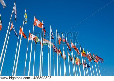 low angle view of flags of various UN members fluttering on wind against cloudless blue sky