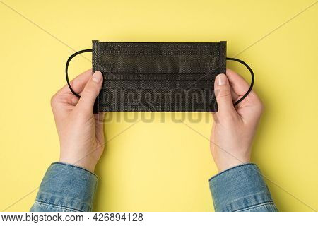 First Person Top View Photo Of Woman's Hand Holding Black Medical Facemask On Isolated Yellow Backgr