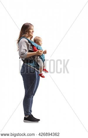Full length profile shot of a mother standing with a baby in a carrier isolated on white background
