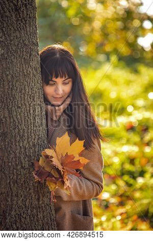 Young Woman In An Autumn Park With A Bouquet Of Bright Fallen Leaves Stands Behind A Tree