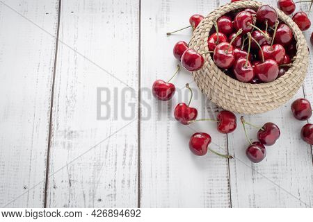Sweet Cherries On A Wooden Background With A Wicker Basket