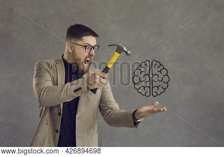 Angry Man Experiencing Mental Disorder, Stress, Or Lack Of Creativity Hitting Brain With Hammer