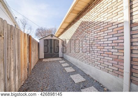 Vinyl Shed In Between A Wooden Fence And Brick Walls Of A House