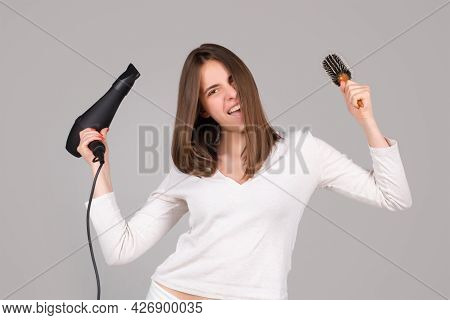 Excited Woman With Hair Dryer. Beautiful Girl With Straight Hair Drying Hair With Professional Haird
