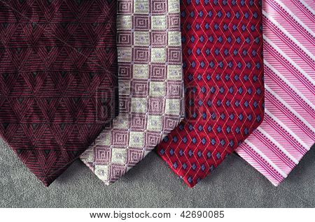 Four ties in tones of red, burgundy and pink in display with a gray background poster
