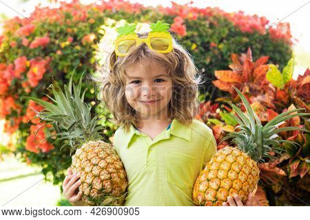 Young Funny Boy Holding Pineapple And Smiling In Backyard. Kid With Pineapple. Kids Summer Fruit.