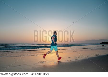 Athletic Young Man Running In The Nature. Sport And Healthy Lifestyle. Man Running On The Beach At S