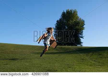 Kid Running Jumping And Flying With Toy Plane Wings On Grass In Park. Child Boy Playing With Toy Air