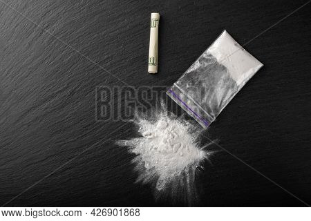 Cocaine In A Plastic Package On A Black Background, Close-up. A Rolled Up Dollar Bill For Drug Use.