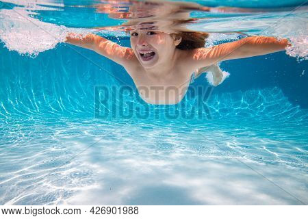 Kid Boy Swim Underwater In Pool. Child Swimming And Diving Underwater In Water Pool. Underwater Kids
