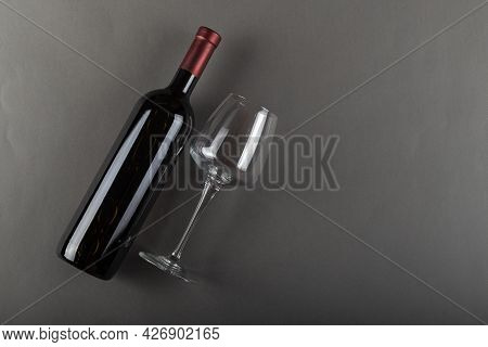 Corked Bottle Of Red Wine And Empty Wine Glass On Gray Background. Alcoholic Drink. Winemaking Conce