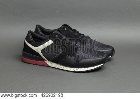 Pair Of Stylish Black Sneakers On A Gray Background. Insulated Footwear.