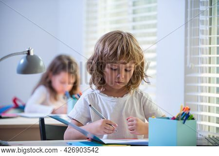 Cute Pupil Writing At Desk In Classroom At The Elementary School. Student Boy Doing Test In Primary