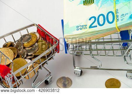 A Bundle Of 200 New Israeli Shekels On A Grocery Cart And A Stack Of Israeli Coins On A Grocery Cart