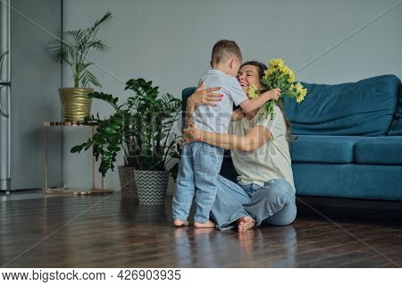 Happy Mother Day. Child Son Congratulates Mother On Holiday And Gives Flowers. Congratulating Her On