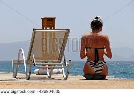 Tanned Girl In Swimsuit Sitting On Wooden Pier Near The Lounge Chair On Sea And Misty Mountains Back