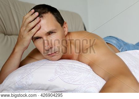 Man Lying On A Bed Putting His Hand On Forehead. Concept Of Headache At Morning, Hangover Or Cold An