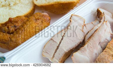 Sliced Pieces Of Cold Baked Pork In A Plastic Container, With Slices Of Wheat Bread And Fried Chicke