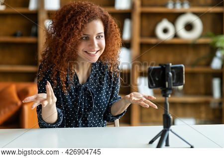 Curly Attractive Woman Speaking To The Camera On The Phone On A Tripod, Gesturing, Blogging Or Speak