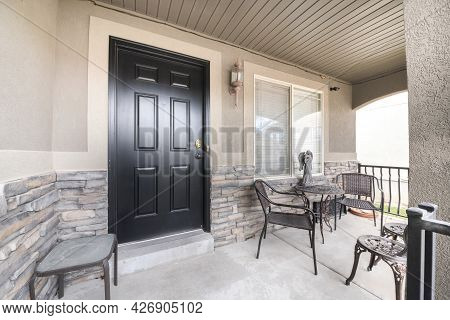 Front Porch Of A House With Black Door And A Stone Bricks Wall Siding