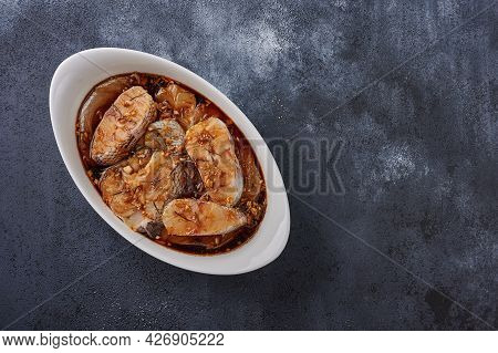 Baked White Sea Fish Macrourus In Marinade Of Olive Oil, Rosemary, In White Pan On Dark Textured Bac