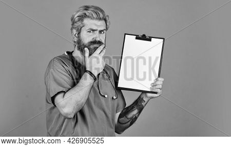 Hospital Treatment. Coronavirus Concept. Man Bearded Doctor With Folder. Seek Urgent Medical Attenti