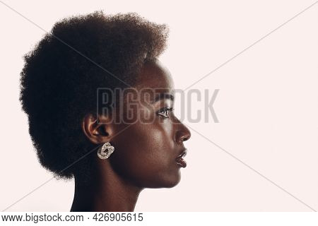Close Up Profile Portrait Of African American Woman With Afro Hairstyle On White Studio Background.