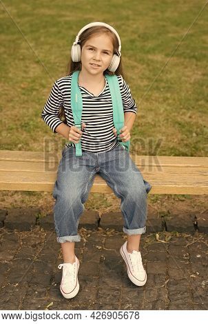 Modern Education. Small Child Wear Headphones Summer Outdoors. Little Girl Listen To Music. Modern T