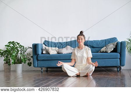 Calm Brunette Doing Yoga On Bed At Home On The Floor