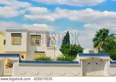 Beautiful Arabic House With White Gate Against Cloudy Sky In Tunisia.
