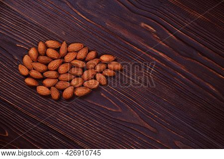 Almonds On Red Wooden Background. Nuts And Copy Space. Almond On A Background Of Mahogany.