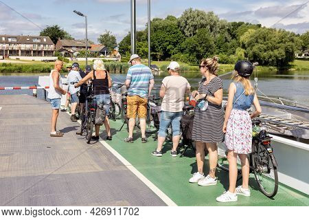 Broekhuizen, The Netherlands - June 19, 2021: Pedestrians And Cyclists At Ferry Crossing Dutch River