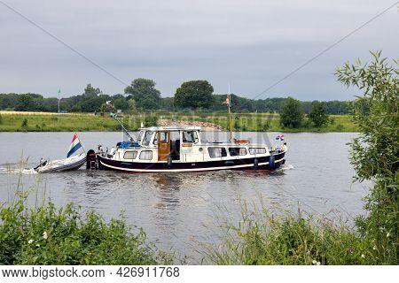 Arcen, The Netherlands - June 24, 2021: Cruiser Sailing Near Arcen At Dutch River Meuse